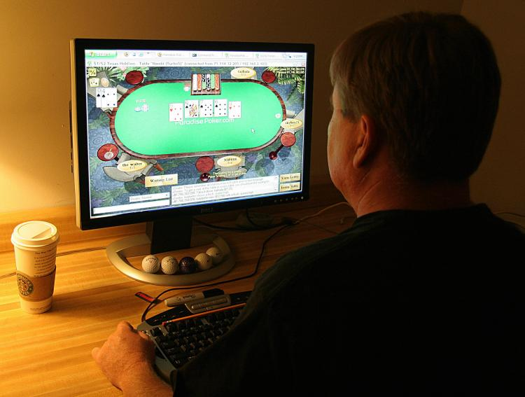 ILLEGAL? In a file photo, a man plays online poker on his computer connected to an internet gaming site from his home in Manassas, Va. Three of the biggest online poker websites were shut down late last week by U.S. authorities. (Karen Bleier/AFP/Getty Images)