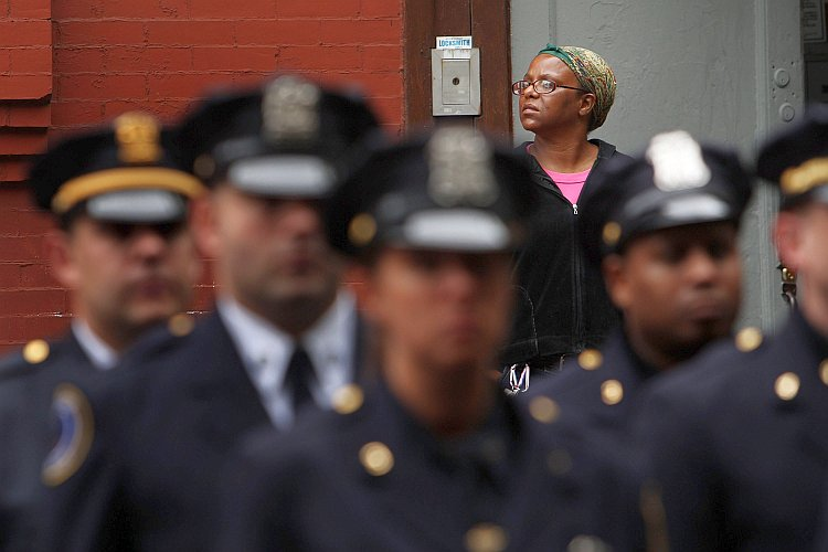 A woman watches as New York City police officers line up