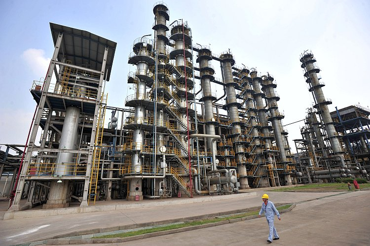 A Chinese worker walks by a Sinopec oil refinery