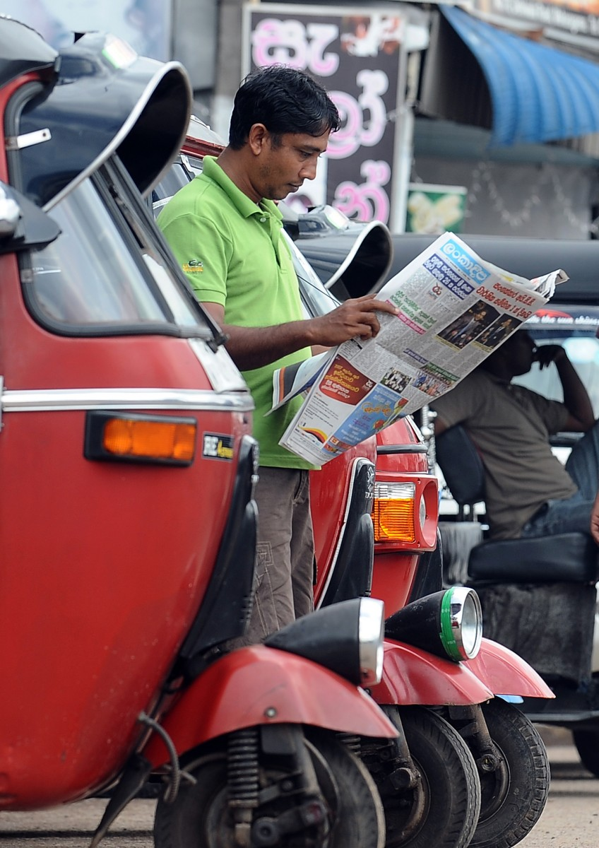 A Sri Lankan man reads a local newspaper in the capital Colombo on Sept. 17, 2012. (Lakruwan Wanniarachchi/AFP/GettyImages)