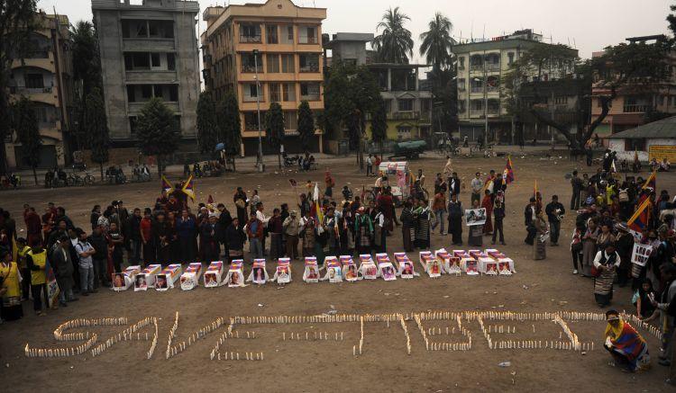 Tibetans offer prayers near mock coffins