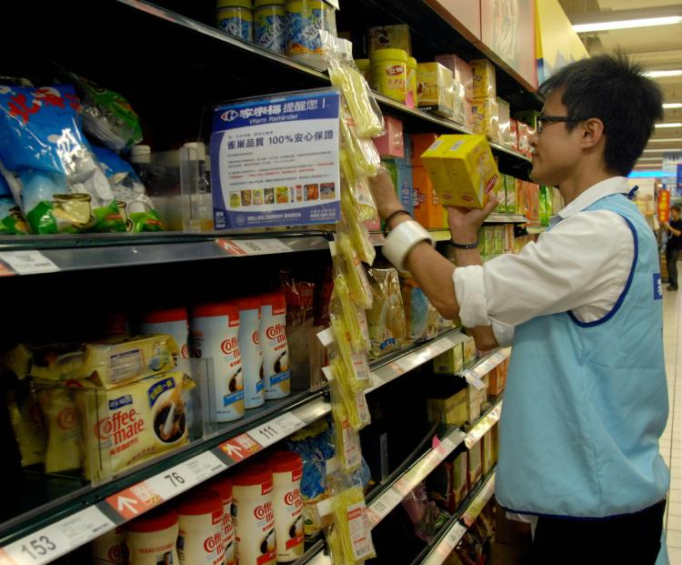 BANNED PRODUCTS: A supermarket employee removes contaminated milk products imported from China from the store's shelves in Taipei, Taiwan last month. (Patrick Lin/AFP/Getty Images)