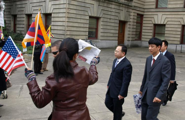 Chinese officials walk toward Tibetan protesters after visiting Portland City Hall on March 8.  (Jampa Lhatsang/www.TibetanPrayerFlag.com)
