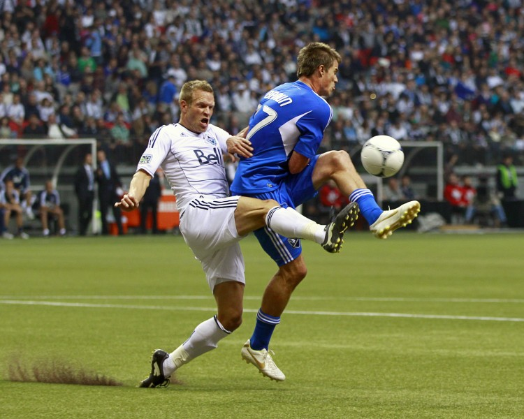 Vancouver's Jay DeMerit (L) challenges Montreal's Justin Braun for the ball in MLS First Kick action Saturday at B.C. Place Stadium. (Jeff Vinnick/Getty Images)