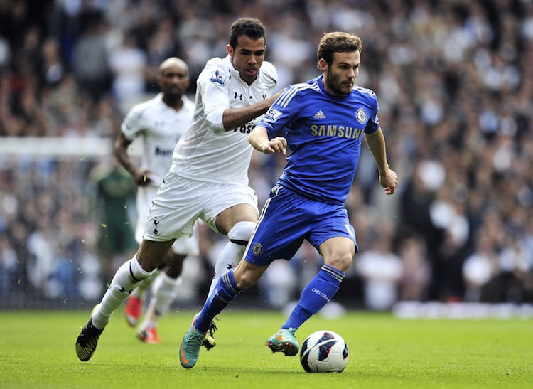 Juan Mata of Chelsea drives pasat Tottenham's Sandro in Saturday's English Premier League London derby match. Mata scored two goals and set up another in a convincing Chelsea win. (Glyn Kirk/AFP/Getty Images)