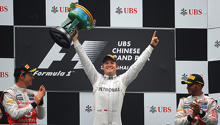 Mercedes-AMG driver Nico Rosberg celebrates his first Formula One win, the Chinese Grand Prix, while McLaren drivers Jenson Button (L) and Lewis Hamilton (R) look on. (Liu Jin/AFP/Getty Images)