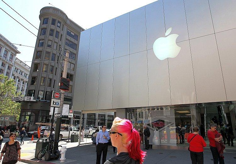 Pedestrians walk by an Apple Store