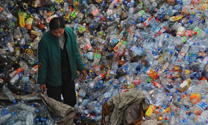 A woman stands amongst a huge pile of used plastic bottles Wuhan of Hubei Province, China on Oct. 29, 2008. (China Photos/Getty Images)