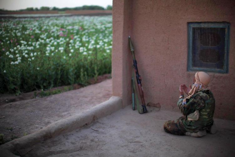 An Afghan National Army soldier prays during a foot patrol with unseen US Marines from India Company, 3rd Battalion, 6th Marines near a poppy field in a stronghold Taliban area of Marjah, Helmand province, southern Afghanistan, on April 5.