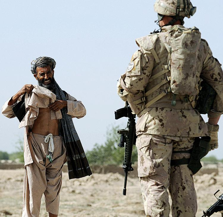 A Canadian soldier with the NATO-led International Security Assistance Force (ISAF) stops an Afghan passer-by during a patrol in Panjwayi district, some 30 kms west of Kandahar province earlier this year. The deaths of two children have brought Canadian s (Shah Marai/AFP/Getty Images)