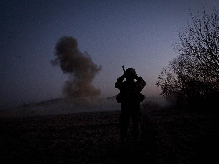 A U.S. soldier from Bravo Troop 1-75 Cavalry 2nd Brigade 101st Airborne Division records video footage while blowing up an Improvised Explosive device (IED) in Zari district of Kandahar province on December 29, 2010. (Behrouz Mehri/AFP/Getty Images)