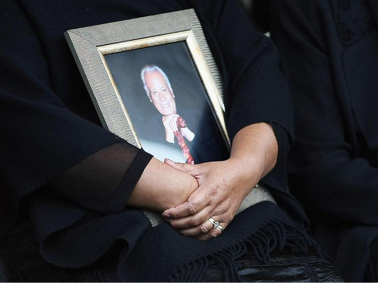 Daughter Donna Grant holds a photo of Sir Howard Morrison during his the burial service at the Kauae cemetery on September 29, 2009 in Rotorua, New Zealand. (Hannah Johnston/Getty Images)