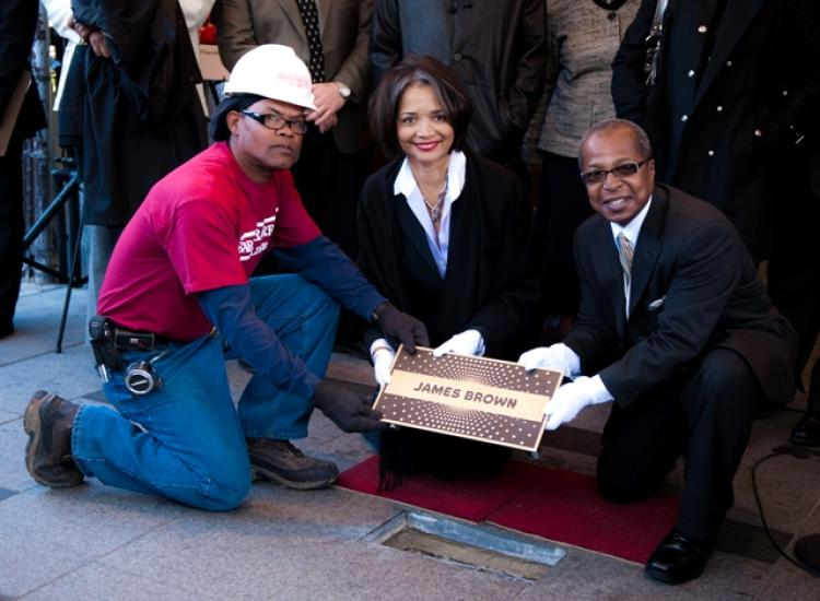 The first star of the Apollo Theater's Walk of Fame is installed for James Brown by (L-R) a construction worker, Apollo Theater's President and CEO Jonelle Procope, and Historian Billy Mitchell. (Aloysio Santos/The Epoch Times)
