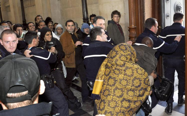 The mother and the brother of Youssouf Fofana leaves Paris' courthouse escorted by policemen as they are threatened by several people, on April 29, 2009, at the end of an audience on the opening day of the trial of Youssouf Fofana.  (Stephane de Sakutin/AFP/Getty Images)