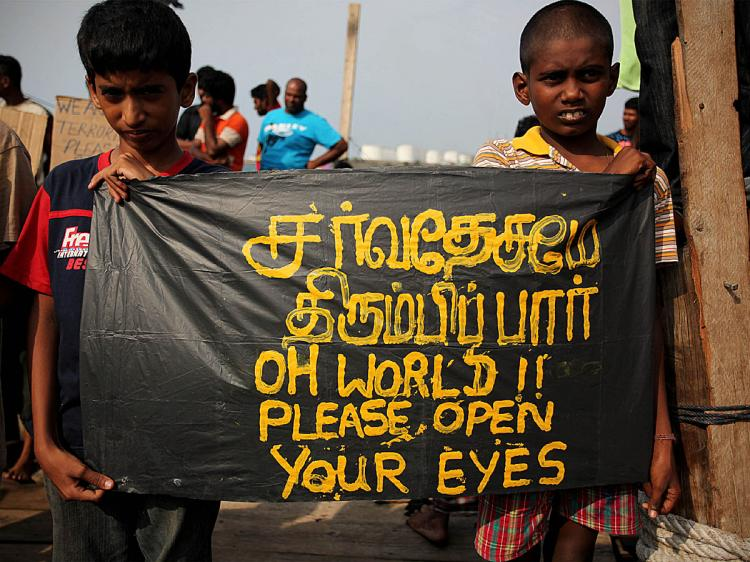 Sri Lankan asylum seekers hold placards during a protest on board a wooden boat demanding the United Nations High Commission for Refugees (UNHCR) to take care of a group of refugees, at Merak seaport on October 28, 2009 in Banten Province, Indonesia. (Ulet Ifansasti/Getty Images)