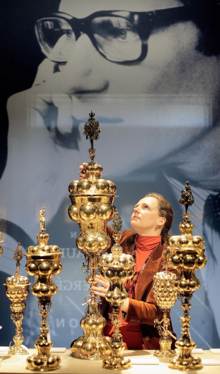 A Christie's employee poses with a a German parcel-gilt table fountain during a tour of an exhibition of 'The Collection of Yves Saint Laurent and Pierre Berge' at Christie's auction house in central London, on Jan. 29, 2009. (Shaun Curry/AFP/Getty Images)