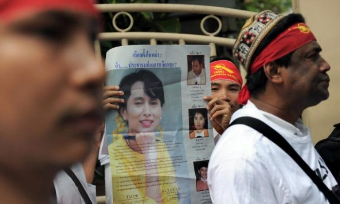 Political activists including exiles from Myanmar hold pictures of democracy icon Aung San Suu Kyi as they head towards the Myanmar embassy to stage a protest in Bangkok on November 7, 2010. (Christophe Archambault/AFP/Getty Images)