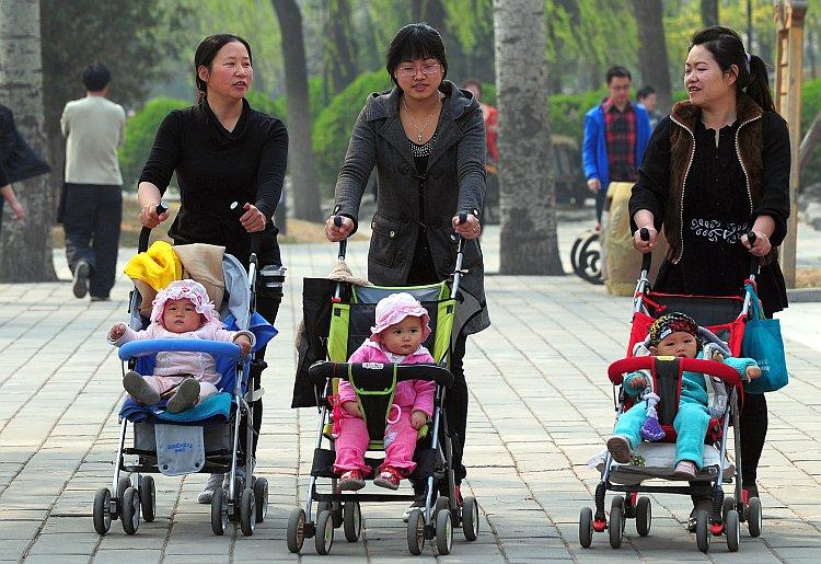 Women push babies in strollers through a Beijing park
