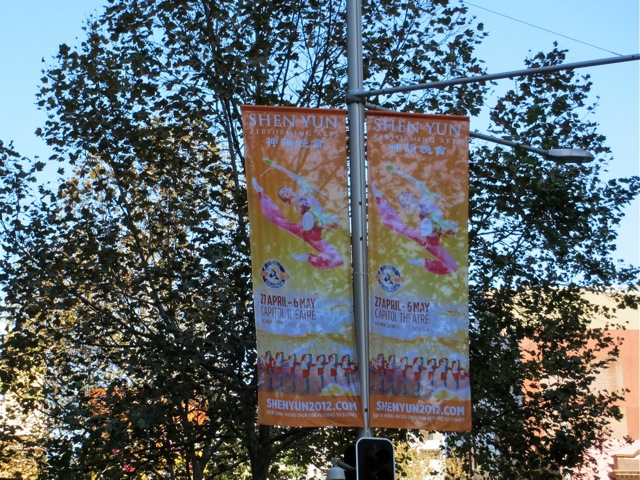 Banners fluttering high above a busy city street.