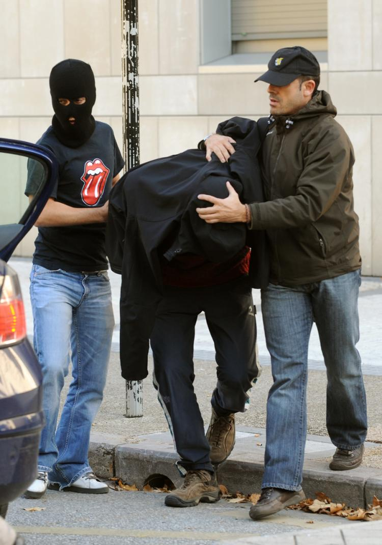 An unidentified person (C), suspected of being a member of Segi, an outlawed youth group believed to have ties to the armed Basque separatist group ETA, is escorted to a police car on November 24, 2009, in the northern Spanish Basque city of San Sebastian. (Rafa Rivas/Getty Images)