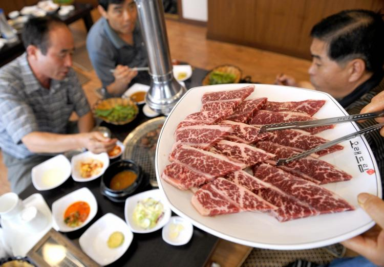 BEEFY: South Koreans taste US beef during a tasting event supported by the Korean Medical Association at a restaurant in Seoul on July 9. The association joined a government-led campaign to dispel public concerns about mad cow disease. (Jung Yeon-Je /AFP/Getty Images)