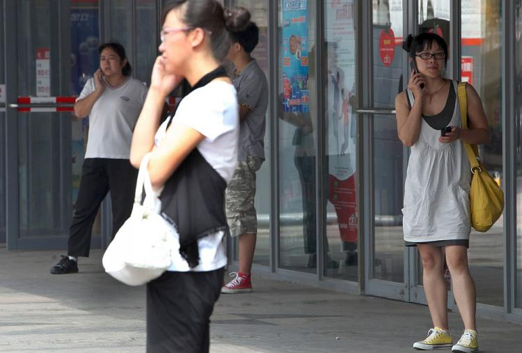Chinese shoppers chat on their cellphones outside a mall in Beijing on September 1, 2010. Beijing will establish 'an information platform containing locations of Beijing citizens' based on the data obtained by tracking and monitoring China Mobile Limited's 17 million mobile phones in Beijing. (Franko Lee/AFP/Getty Images)
