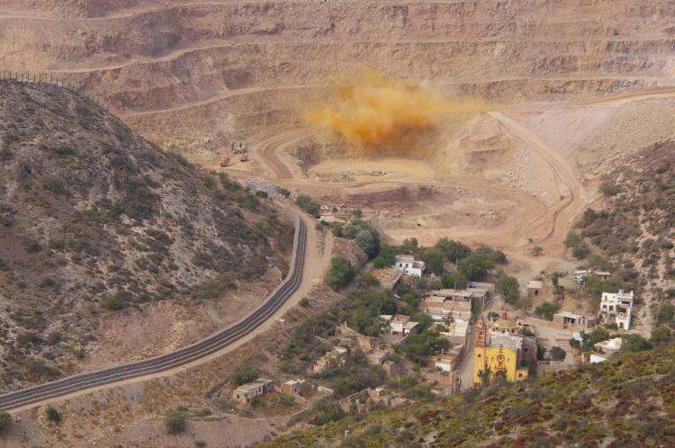 Rock blasting at the Cerro de San Pedro open-pit gold and silver mine in Mexico. The town buildings can be seen in the forefront.