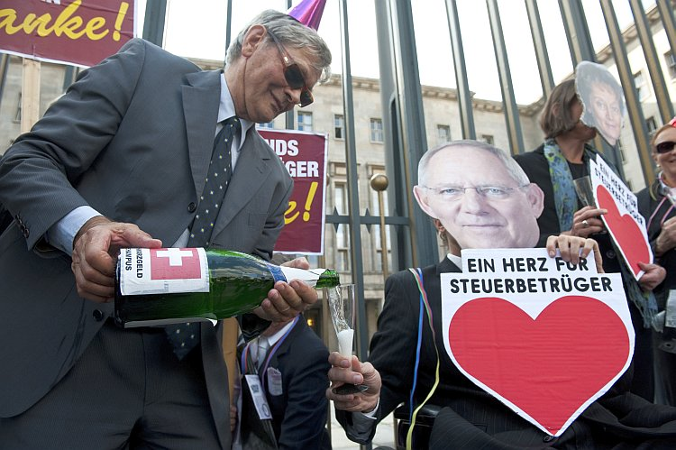 A demonstrator carrying a bottle of 'Schwarzgeld' (dirty money) champagne