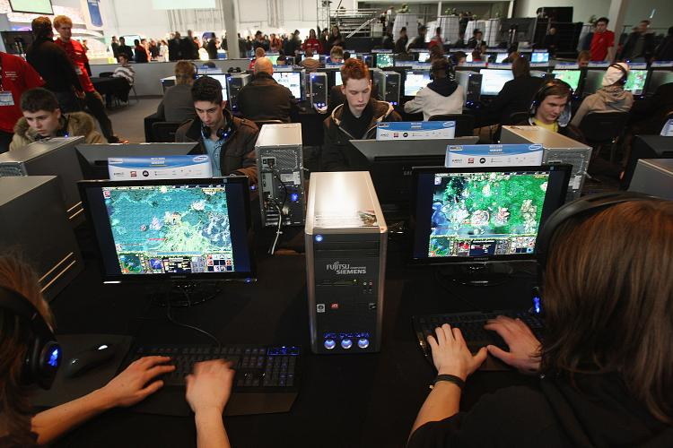 Visitors play video games on desktop computers at the CeBIT technology fair in Hanover, Germany, March 4, 2008.  (Sean Gallup/Getty Images  )