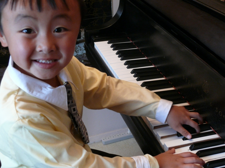 Six-year-old Xiaoping Wang plays the piano with the skill and confidence of someone years older. (The Epoch Times)