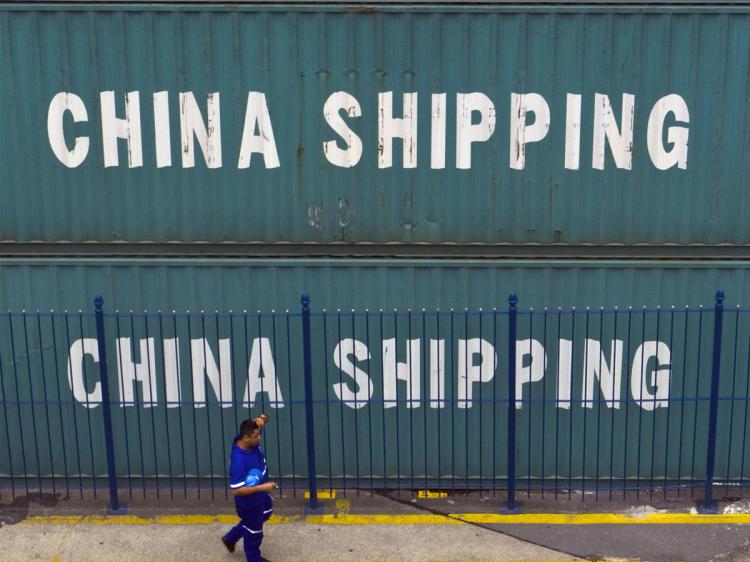 A port employee walks next to containers coming from China and waiting to be loaded to return with Brazilian goods, in Rio de Janeiro's port on February 6, 2009. (Antonio Scorza/AFP/Getty Images)