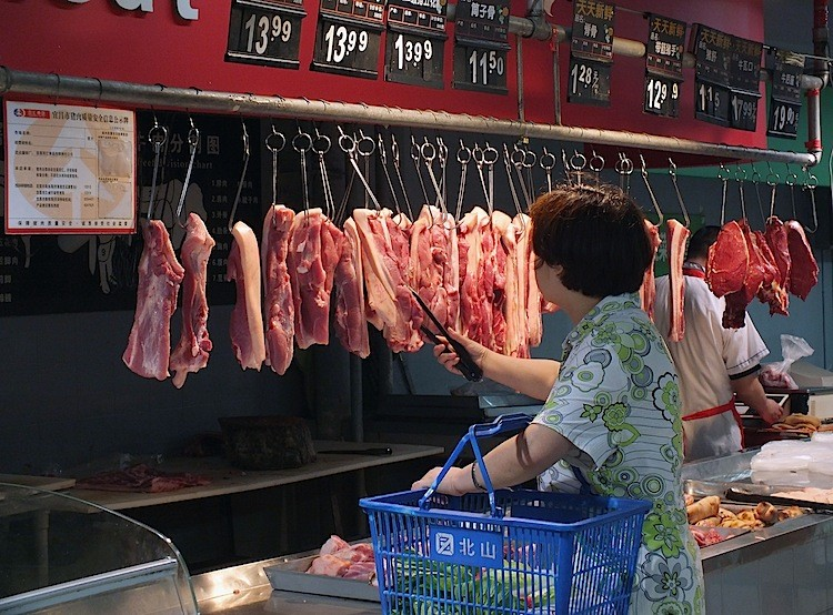 A woman buys pork at a supermarket on July 3 in Yichang, Hubei Province. China's consumer price index (CPI), a main gauge of inflation, surged 6.4 percent over last year, hitting a three-year high in June. Grains rose 12.4 percent, eggs 23.3 percent, and pork soared a whopping 57.1 percent. (AFP/Getty Images)