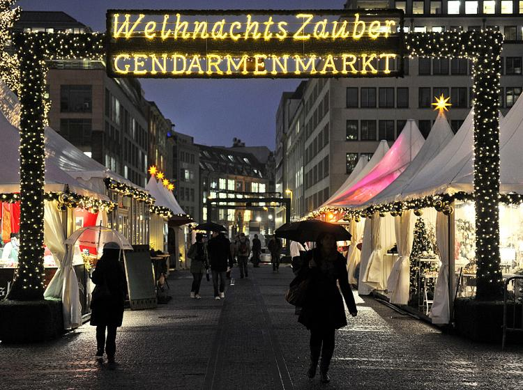GERMANS SPENDING AGAIN: A few shoppers brave the rain to attend the opening day of the Christmas market at Gendarmenmarkt in Berlin, Nov. 22, as the Christmas shopping season starts. German consumer spending growth hit a 5-year-high last month and retailers are very optimistic about the holiday season. (Odd Andersen/AFP/Getty Images)