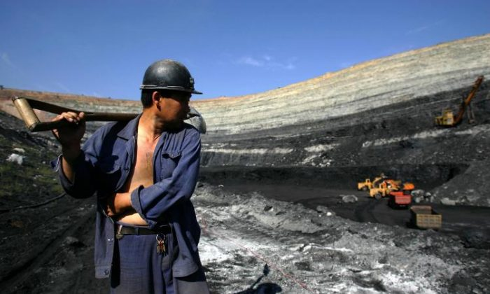 A coal miner walks on coal seams in an open pit coal mine in Chifeng of Inner Mongolia Autonomous Region, China on Aug. 19, 2006. (China Photos/Getty Images)