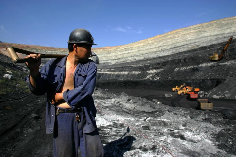 A coal miner walks on coal seams in an open pit coal mine on Aug. 19, 2006, in Chifeng of Inner Mongolia Autonomous Region, China. Many privately owned coal mines are being assimilated into larger state-run companies at a loss to the owners. (China Photos/Getty Images)