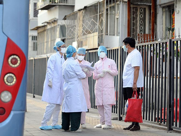 Chinese medical personnel check the Beijing neighborhood near a hostel where a group of school children are quarantined after seven people in their school were diagnosed with the swine flu, July 2, 2009. (AFP/Getty Images)