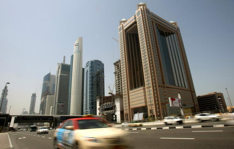 Cars drive past skyscrapers on Sheikh Zayed Road in the Gulf emirate of Dubai. The Dubai investment company Dubai World agreed on Thursday to restructure around $23.5 billion in debt, to reduce its debt obligations by nearly 40 percent. (Karim Sahib/AFP/Getty Images)