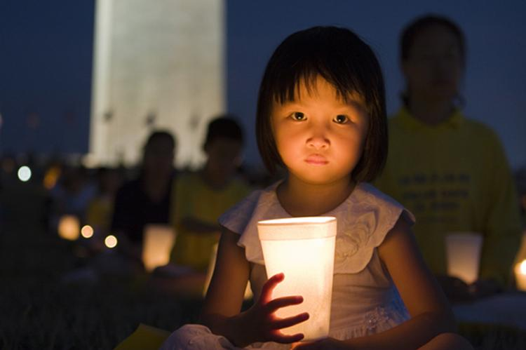 A young girl is illuminated by candle light during the commemorative vigil on July 18. (Shaoshao Chen/The Epoch Times)