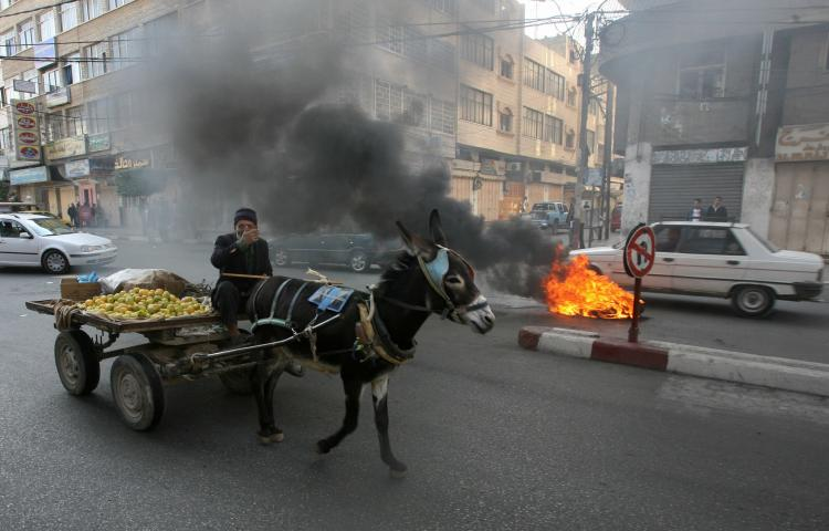A Palestinian man rides on his donkey cart past burning tires in Gaza. A similar donkey-drawn wagon was rigged with an explosive device and detonated at the Gaza security fence on Tuesday morning.  (Mahmud Hams/Getty Images)