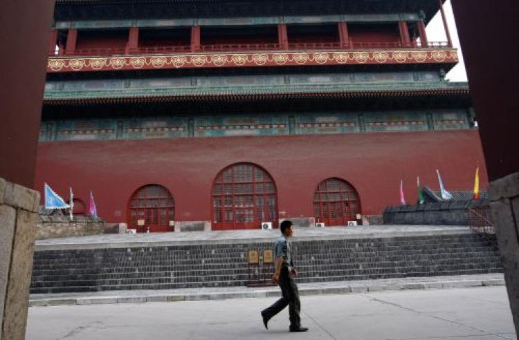 A Chinese policeman walks by the Drum Tower where an American tourist was killed August 9, 2008 in Beijing. Some believe that the Chinese Regime is attempting to spread rumors about the incident, linking it with Falun Gong. (Paula Bronstein/Getty Images)