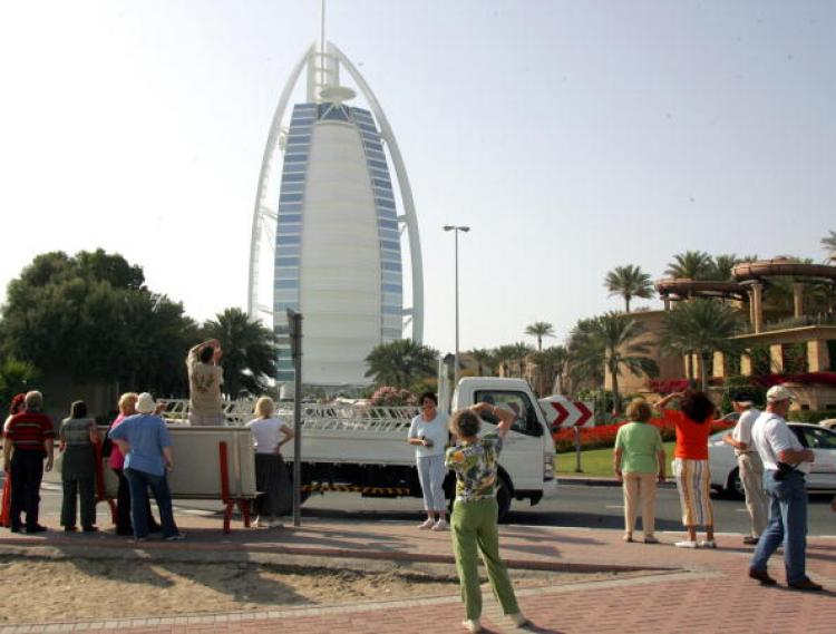 European tourists take pictures of the Burj al-Arab (L) and Jumeirah Beach Hotel in Dubai.  (Rabih Moghrabi)