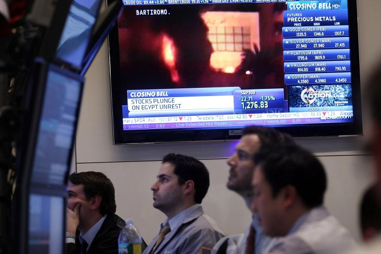With a television screen showing images of the unrest in Egypt, traders work on the floor of the New York Stock Exchange (NYSE) at the end of the trading day on Jan. 28 in New York City. As investors fears of the protests in Egypt spread through the region, U.S. stocks fell Friday afternoon with the Dow losing 166 points. (Spencer Platt/Getty Images)