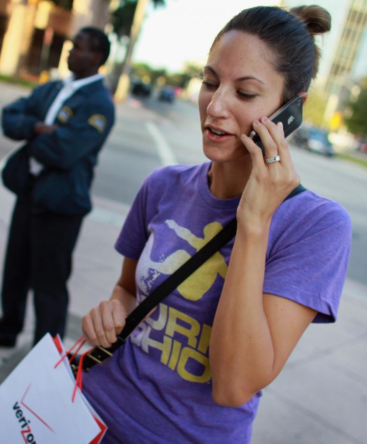 TRACKED: Julie Bennink makes a phone call on her iPhone in Coral Gables, Fla. Apple reportedly tracks customers' location data through its management software iTunes. (Joe Raedle/Getty Images)