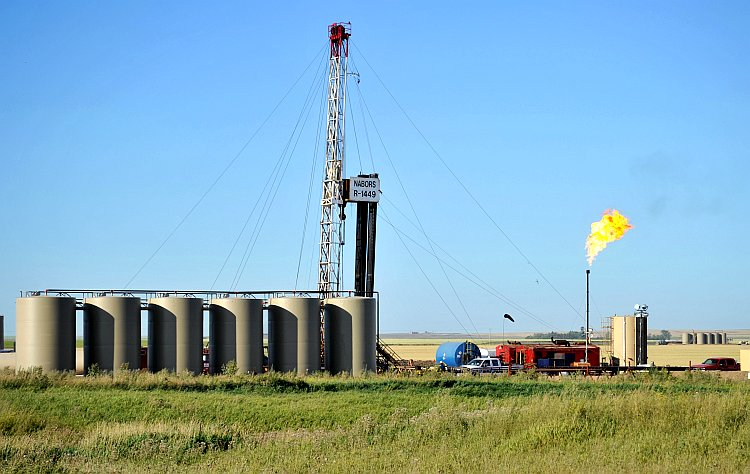 Natural gas is burned off next to an oil well being drilled by workers