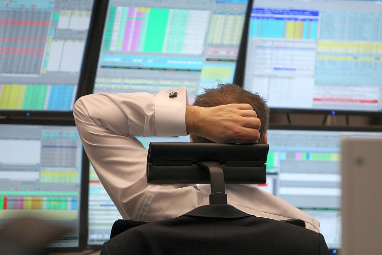 A broker sits in front of screens showing the German market rates