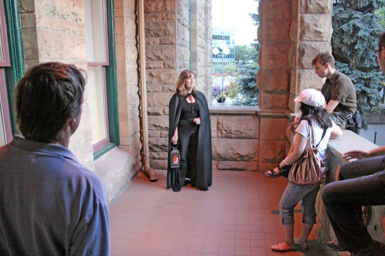 Calgary Ghost Tours Owner/Operator Johanna Lane describes the story of a politician shot in a card game in the basement of Old City Hall who reportedly now haunts the site. (The Epoch Times)