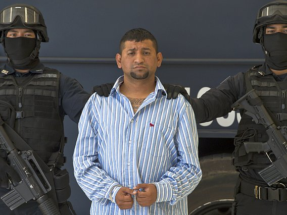 """Mexican Federal police personnel escort  David Rosales Guzman, aka """"Commander Devil"""",  alleged member of the Gulf cartel,  during his presentation to the press at the Police Command Centre in Mexico City on September 02, 2012. According to the Mexican authorities , Rosales Guzman  was in charge of the illegal drug trafficking In Monterrey, north Me"""