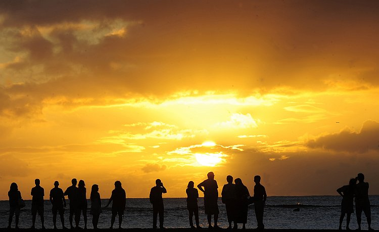 People gather to watch the sunset from Waikiki Beach in Honolulu, Hawaii