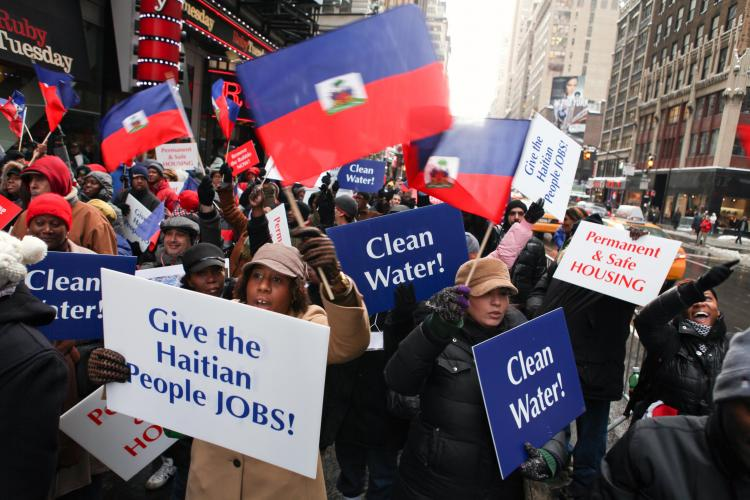 Marking the one-year anniversary of the massive earthquake in Haiti, Haitians and supporters rallied in Times Square and subsequently marched to the Haitian Consulate in New York City on Wednesday to urge faster relief for the country.  (Amal Chen/The Epoch Times)