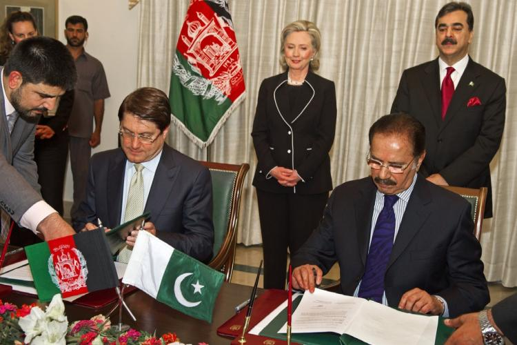 Afghanistan Minister of Trade Anwar Ul Haq Ahadi (L) and Pakistani Minister of Trade Makdoom Amin Fahim (R-front) sign treaties, including a trade deal, as U.S. Secretary of State Hillary Clinton and Pakistani Prime Minister Syed Yousaf Raza Gillani look on. (Paul J. Richards/Getty Images)